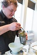 Matthew väger upp blomknoppar från plantan cannabis sativa till en kund på The Agresic, Corvallis, Oregon, USA