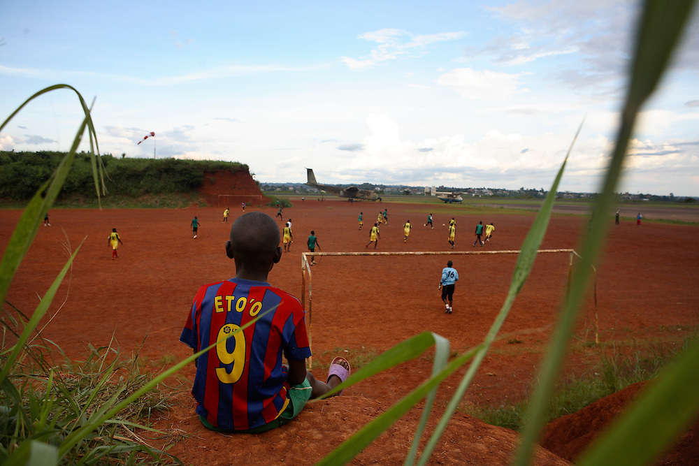 Paul, 13 a young Eto'o and Cameroon fan watches the team AS Pelican FC play training match on a pitch next to the military sirport. Yaounde, Cameroon.