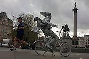 A jogger runs through Trafalgar Square, passing a street artist busker on a painted bike.