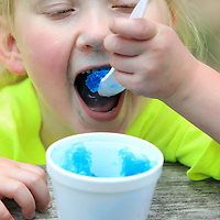 Isabella Taylor, 6, from Myrtle, enjoys eating her blueberry snow cone that her dad Brent bought for her from the Rockin' Robin Shaved Ice & Refreshment stand at Ballard Park on Labor Day.