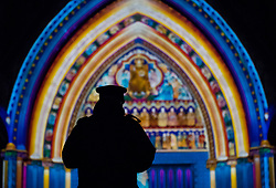 © Licensed to London News Pictures. 17/01/2018. London, UK. A security guard looks at Westminster Abbey's North Door  lit by French artist Patrice Warrener - 'The Light of the Spirit Chapter 2' - during the Lumiere London festival. Running from 18th-21st January 2018 more than 50 artworks are transforming the capital's streets, buildings and public spaces into an immersive nocturnal art exhibition of light and sound. Locations include King's Cross, Fitzrovia, Mayfair, West End, Trafalgar Square, Westminster, Victoria, South Bank and Waterloo. Photo credit: Peter Macdiarmid/LNP