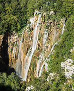 Plitvica River plunges 250 feet over a cliff at Big Waterfall (Veliki Slap) at the beginning of the Lower Lakes (Donje jezera) trails. Plitvice Lakes National Park (Nacionalni park Plitvicka jezera, in Croatia, Europe) was founded in 1949 and is honored by UNESCO as World Heritage Site. Waters flowing over limestone, dolomite, and chalk in this karstic landscape have, over thousands of years, deposited travertine barriers, creating natural dams, beautiful lakes and waterfalls. Warming conditions after the last Ice Age (less than 12,000 years ago) allowed the natural dams to form from tufa (calcium carbonate) and chalk depositing in layers, bound by plants. Plitvicka Jezera is a municipality of Lika-Senj County, in the Republic of Croatia.