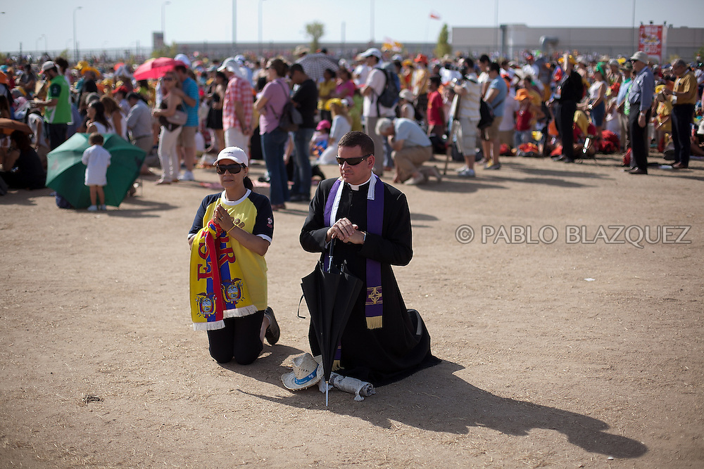 A pilgrim and priest pray during a mass celebrated by Pope Benedict XVI at the base of Cuatro Vientos, eight kilometres (five miles) southwest of Madrid on August 21, 2011. The next World Youth Day festival of the Roman Catholic Church will be held in Rio de Janeiro in 2013, Pope Benedict XVI announced Sunday in Madrid