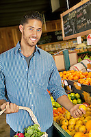 Portrait of handsome young man shopping for fruits in market