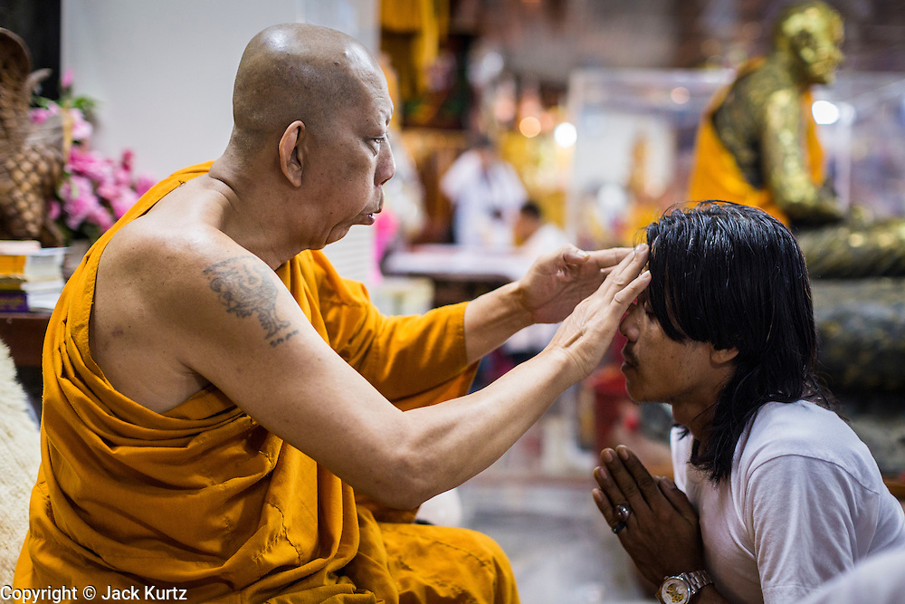 "15 MARCH 2014 - NAKHON CHAI SI, NAKHON PATHOM, THAILAND: A senior monk at Wat Bang Phra blesses a man at the beginning of the tattooo festival. Wat Bang Phra is the best known ""Sak Yant"" tattoo temple in Thailand. It's located in Nakhon Pathom province, about 40 miles from Bangkok. The tattoos are given with hollow stainless steel needles and are thought to possess magical powers of protection. The tattoos, which are given by Buddhist monks, are popular with soldiers, policeman and gangsters, people who generally live in harm's way. The tattoo must be activated to remain powerful and the annual Wai Khru Ceremony (tattoo festival) at the temple draws thousands of devotees who come to the temple to activate or renew the tattoos. People go into trance like states and then assume the personality of their tattoo, so people with tiger tattoos assume the personality of a tiger, people with monkey tattoos take on the personality of a monkey and so on. In recent years the tattoo festival has become popular with tourists who make the trip to Nakorn Pathom province to see a side of ""exotic"" Thailand.   PHOTO BY JACK KURTZ"