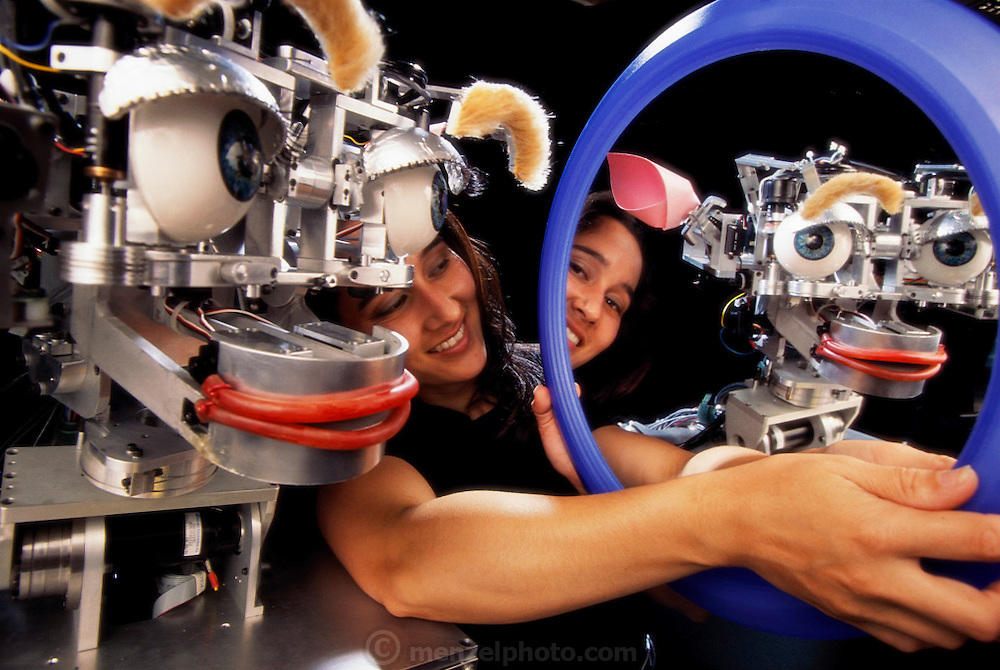 MODEL RELEASED. Kismet robot interacting with a mirror held by researcher Cynthia Breazeal. Kismet is a robot that responds with facial expressions to her actions. It has been developed for the study of action recognition and learning, particularly in children. Kismet has several moods, which it displays as expressions on its face. It responds to visual stimuli like a baby. When there are no stimuli, it shows a sad expression. When paid attention to, as here, Kismet looks interested. Like a child, Kismet responds best to bright colours and moderate movements. Photographed at Massachusetts Institute of Technology (MIT), Cambridge, USA.