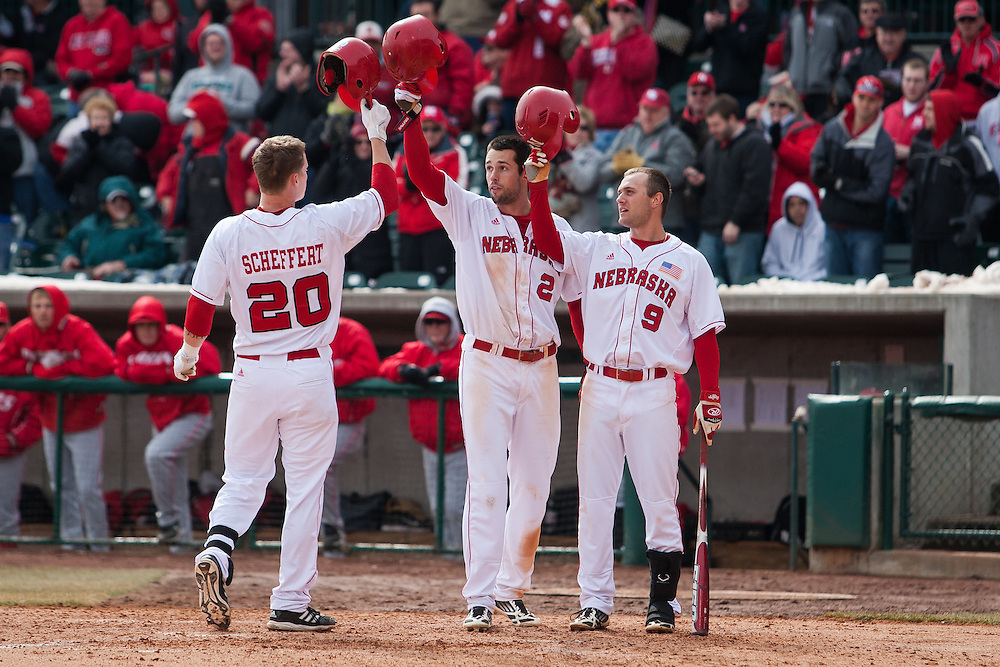 March 03, 2013: Nebraska's Josh Scheffert #20 steps across home plate after hitting a homer in the sixth with Chad Christensen #2 and Pat Kelly #9 to congratulate him in the game against New Mexico during the second game of the two game series at Haymarket Park in Lincoln, Nebraska. Nebraska defeated New Mexico 3 to 0.