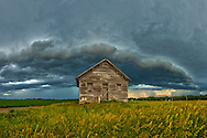 An old house sits on the prairie as a storm moves overhead.<br />