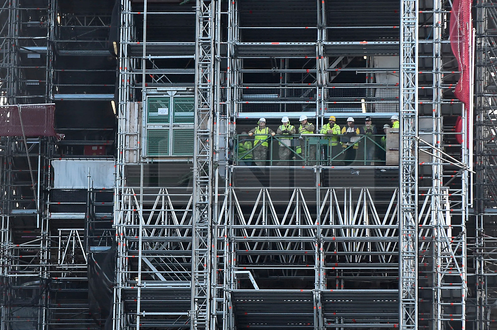 © Licensed to London News Pictures. 11/11/2018. LONDON, UK.  Workmen in the Elizabeth Tower view the thousands of people gathered in Parliament Square on Remembrance Sunday which, this year, marks the centenary of Armistice Day.  Big Ben, the bell inside the Elizabeth Tower, currently undergoing renovation, has been given a special makeover in order to chime at 11am.  Photo credit: Stephen Chung/LNP