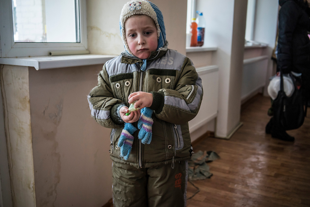 A young boy is bundled up against winter cold after walking to the communal dining area for lunch at Romashka, a summer camp where he and several hundred other people live after being displaced by fighting in Eastern Ukraine on Friday, February 13, 2015 in Kharkiv, Ukraine.