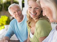Three people sitting on verandah