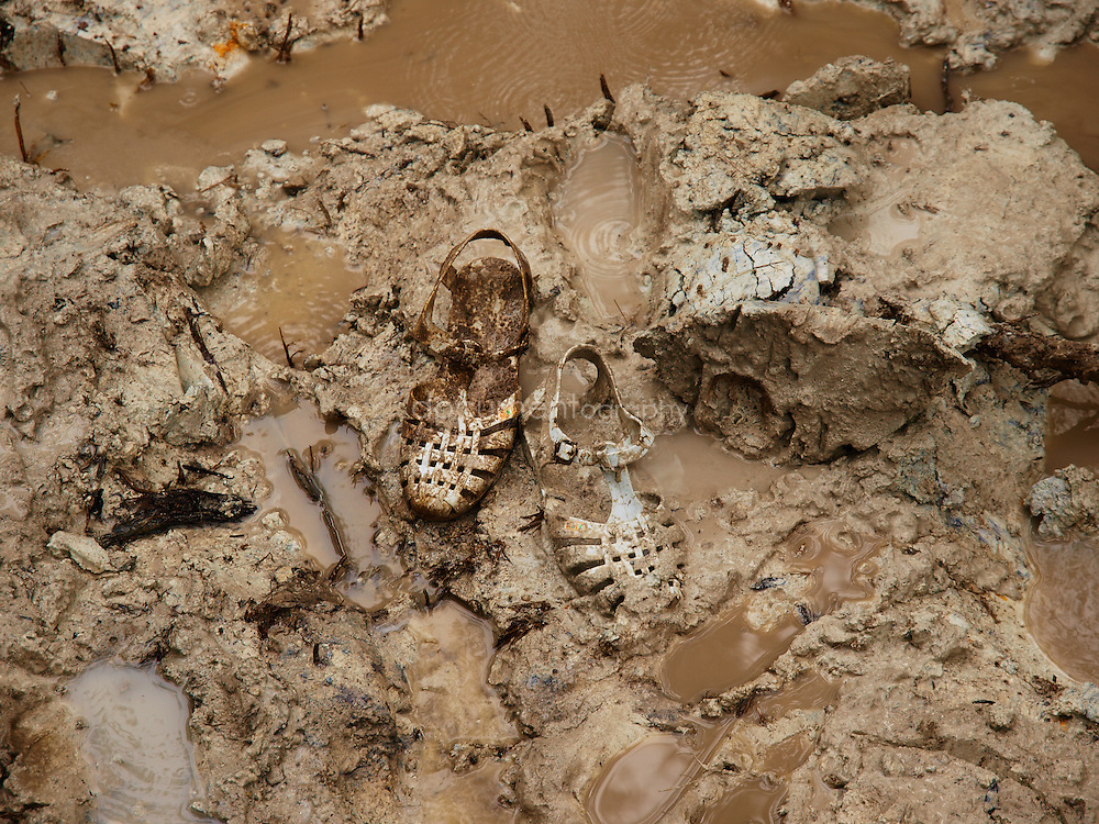 A pair of sandals in the mud, belonging to a miner searching for diamonds and gold, Manamu, Kingsville, Liberia.
