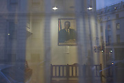 Framed portrait of Zimbabwe President Robert Mugabe through window of London embassy.