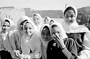 Crowd of school girls in full traditional clothing in a schoolyard, laughing