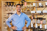 Portrait of a handsome man standing with hands on hips in lights store