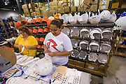 Kelly Gillespie, left, and Keila Marrero, right, both of Lorain adhere the stickers on hundreds of football helmets at sports equipment manufacturer Riddell in Elyria, Ohio on July 29, 2009.