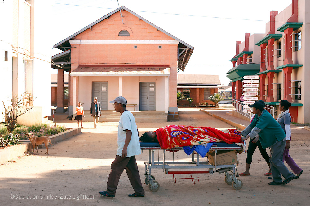 A pregnant lady being pushed on a trolley across the hospital car park from the delivery room to the operating  theatre ahead of her Caesarean section. Her waters broke 1 week ago and this is her 7th child. Antsirabe Hospital. Antsirabe Clinic Project sponsored by the Swedish Postal Code lottery. Madagascar. September 2015.<br /> (Operation Smile Photographer &ndash; Zute Lightfoot)