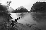 Two young kids play along a river bank in Khammouane Province, Laos, Southeast Asia. Ducks wander near a small boat moored on shore waiting to carry passengers across the river.
