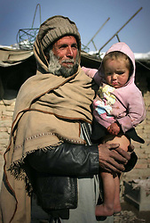 An Afghan man holds his son outside of his tent at a refugee camp, Kabul, Afghanistan, January 2, 2013. Photo by Imago / i-Images...UK ONLY