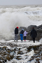 ***CAPTION CORRECTION** © London News Pictures. 08/02/2014. Porthcawl, UK. A family take a risk by walking on wave covered rocks in Porthcawl, wales during a gale force storm which created giant waves.. Photo credit : Graham M. Lawrence/LNP.