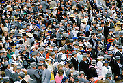 Crowds of spectactors in traditional top hats and tails at Epsom Racecourse for Derby Day, UK