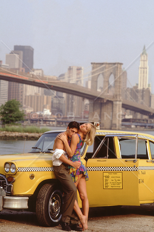 sexy couple embracing and touching in New York City by a taxi cab