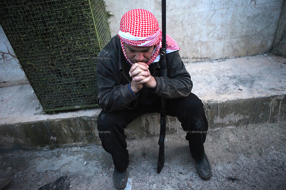 A fighter of the Free Syrian Army mourns in front of the mosque where the bodies of some killed villagers are layed down for identification. On 22. February the syrian army attacked the village of Kureen, Province of Idlib, Syria. Kureen was among the first villages in the northwest of Syria controlled by the opposition. Some villagers and members of the defence units escaped to surrounding olive orchards, when the attack begun in the early morning. A majority of the inhabitants didn´t manage to escape. The heavy shelling lasts 7 houres. Soldiers searched all houses, burnt some of them down, loote shops, stole cars and furniture. About 60 motorcycles were burnt down. Tanks demolished several houses. 6 men were executed. One woman died as a result of an heart attack.