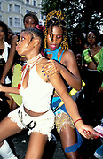 Two girls dancing together, one in a white outfit, Notting Hill Carnival, UK, 1997