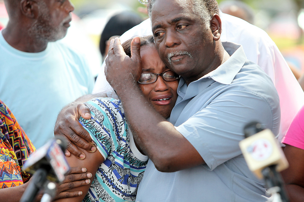 Lonese Lang, 21, is comforted Thursday by Elder James Johnson during a news conference in which the NAACP discussed the investigation into the shooting death of Lang's brother, 19-year-old Denzel Curnell, during a June 20 encounter with a Charleston police officer outside the Bridgeview Village apartments. (ANDREW KNAPP/STAFF)