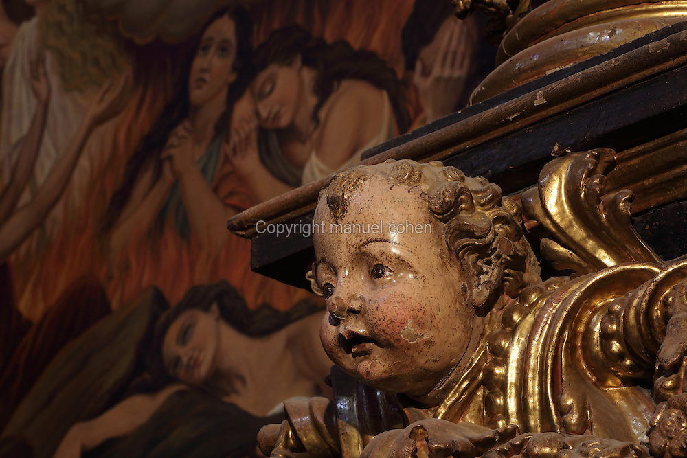 Sculptural detail of the head of a cherub, from the Baroque altarpiece dedicated to the Verge del Carme and the Souls of Purgatory, in the Capelle de la Verge del Carme o de les Animes, 16th century, in the Cathedral of St Mary, designed by Benito Dalguayre in Catalan Gothic style and begun 1347 on the site of a Romanesque cathedral, consecrated 1447 and completed in 1757, Tortosa, Catalonia, Spain. The cathedral has 3 naves with chapels between the buttresses and an ambulatory with radial chapels. Picture by Manuel Cohen