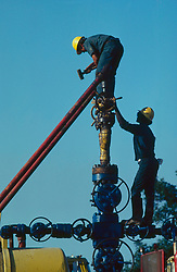 Stock photo of oilfield workers assembling secondary recovery pipe onto christmas tree valve assembly in East Texas.