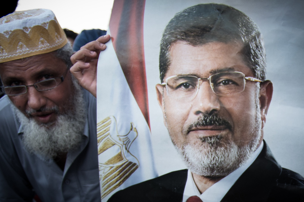 A supporter of ousted President Morsi is holding a poster with the face of Morsi during a rally in front of the Republican Guard Headquarters in Cairo, Egypt, July 5, 2013