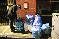 "© Licensed to London News Pictures . 22/12/2018 . Manchester , UK . A man urinates on to and then collapses over a pile of rubbish sacks on Jerusalem Place . Revellers out in Manchester City Centre overnight during "" Mad Friday "" , named for historically being one of the busiest nights of the year for the emergency services in the UK . Photo credit : Joel Goodman/LNP"