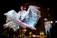 "Two dancers perform La Bamba, a traditional Mexican dance symbolic of marriage. The beautiful woman dancer holds her skirt wide as she turns showing off its pretty lace and ruffles as the man, also dressed in white, works on ""tying to knot"" of a large ribbon as is custom in the dance."