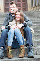 Full length of young couple sitting on steps outdoors