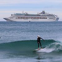 Jacob surfing the spit as a cruise liner departs Dunedin Harbour ,