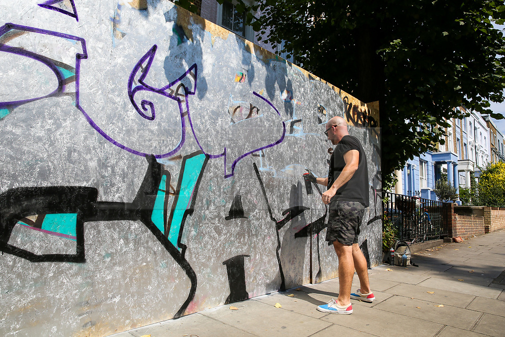 © Licensed to London News Pictures. 24/08/2019. London, UK. A graffiti artist graffiti on the boards up ahead of the 2019 Notting Hill Carnival which takes place this weekend and on bank holiday Monday. Up to 1 million people are expected to attend the biggest street party in Europe. Photo credit: Dinendra Haria/LNP