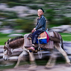 Boy riding a donkey near Pendjikent, Tajikistan, Asia