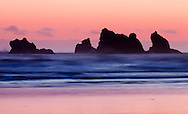 The sun sets behind the western horizon, casting the offshore sea stacks into shadow, Bandon, Oregon