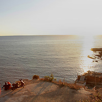 A couple sit along cliffs along the Mediterranean Sea in Beirut, Lebanon.