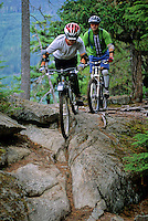 Dad and son, 12, mountain bike on Cut Yer Bars trail, Whistler BC
