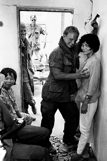 American GIs play with Vietnamese prostitutes in bombed out building near Saigon during the Vietnam War