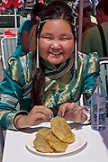 Baden bei Wien, Lower Austria. Naadam Festival of OTSCHIR (Austrian-Mongolian Society) at the Trabrennbahn.<br /> Girl in traditional dress eating Chuushuur (Mongolian dumplings).
