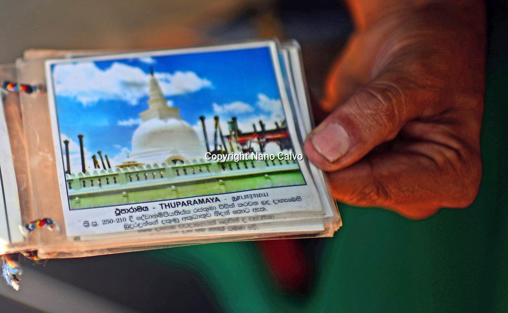 Hand of guide showing photo of Thuparamaya, Anuradhapura, Sri Lanka