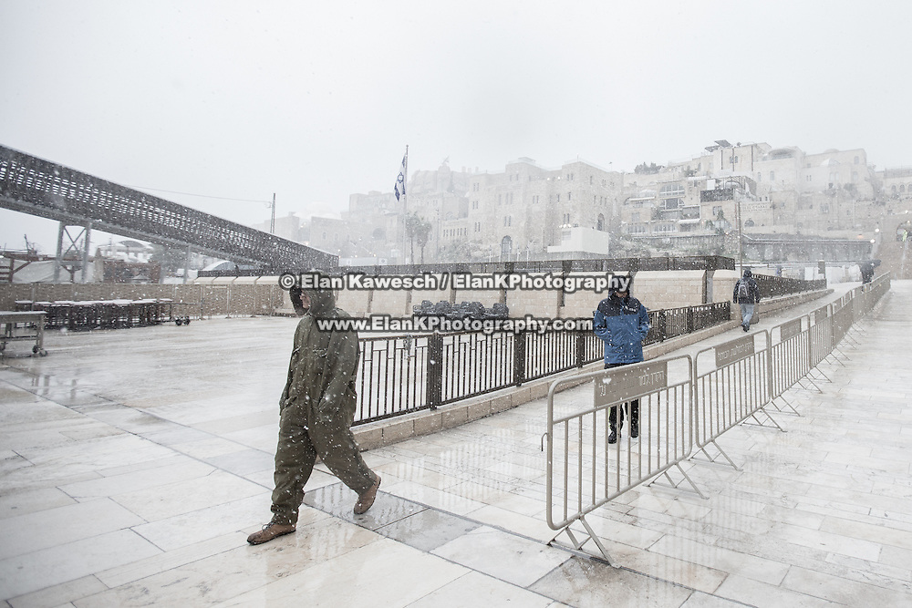 People approach The Kotel as snow and rain fall at The Western Wall on January 7, 2015 in Jerusalem, Israel. (Photo by Elan Kawesch)
