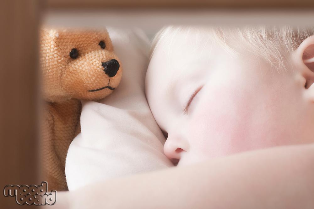 Baby boy lies with teddy bear sleeping