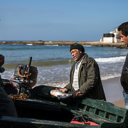 Un homme vient acheter son poisson directement au retour des pêcheurs.