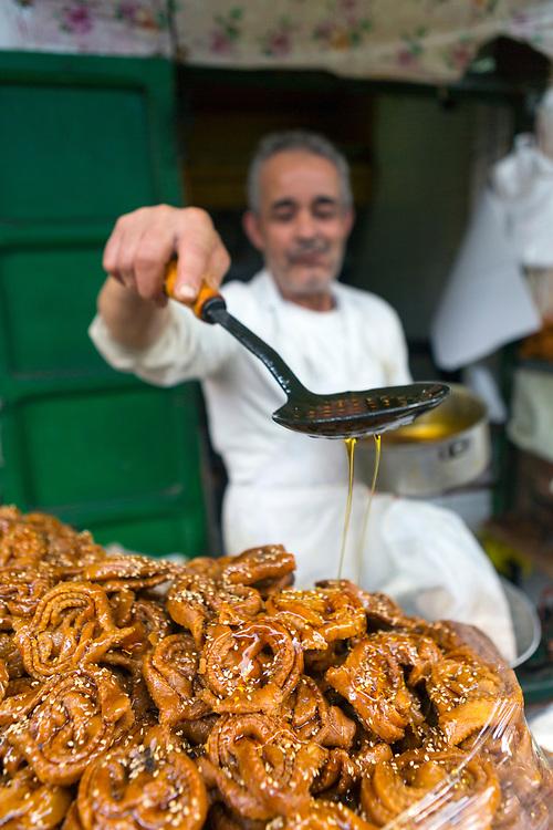TETOUAN, MOROCCO - 5th April 2016 - A street food vendor prepares Moroccan chebekia and birouat street food at his stall in the Tetouan Medina, Rif region of Northern Morocco.