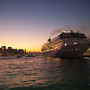 A huge cruise ship has moored up on the Kowloon side of Hong Kong harbour, the sun is setting and the night lights are coming on.
