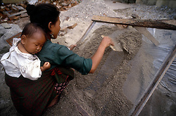 KATHMANDU, NEPAL - OCTOBER 1992 - A Nepalese woman cleans sand by sifting it through a screen while her baby sleeps on her back. Women's rights have been a controversial issue in Nepalese society, where women don't enjoy the same rights that men do such as the right to own land. (PHOTO © JOCK FISTICK)